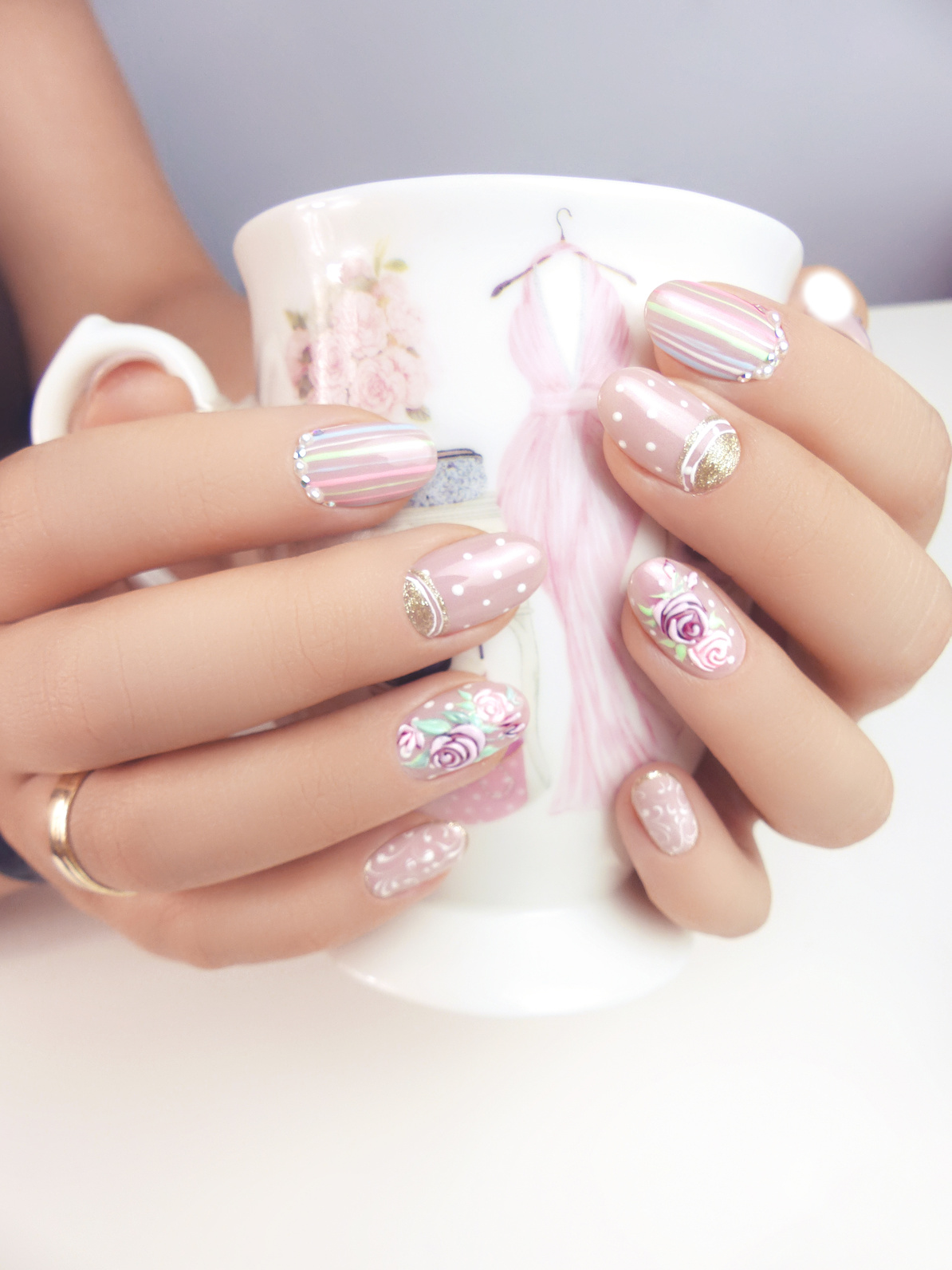 Zwei Hände zeigen bunte Gelnägel in Pastell