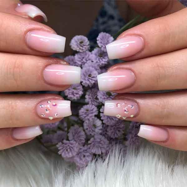 Eine Frau trägt Nägel mit Make Up UV Gel und hält Blumen in der Hand